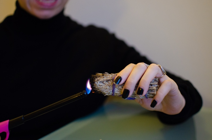 Nadia's hand holding sage while they lit it with a long lighter.