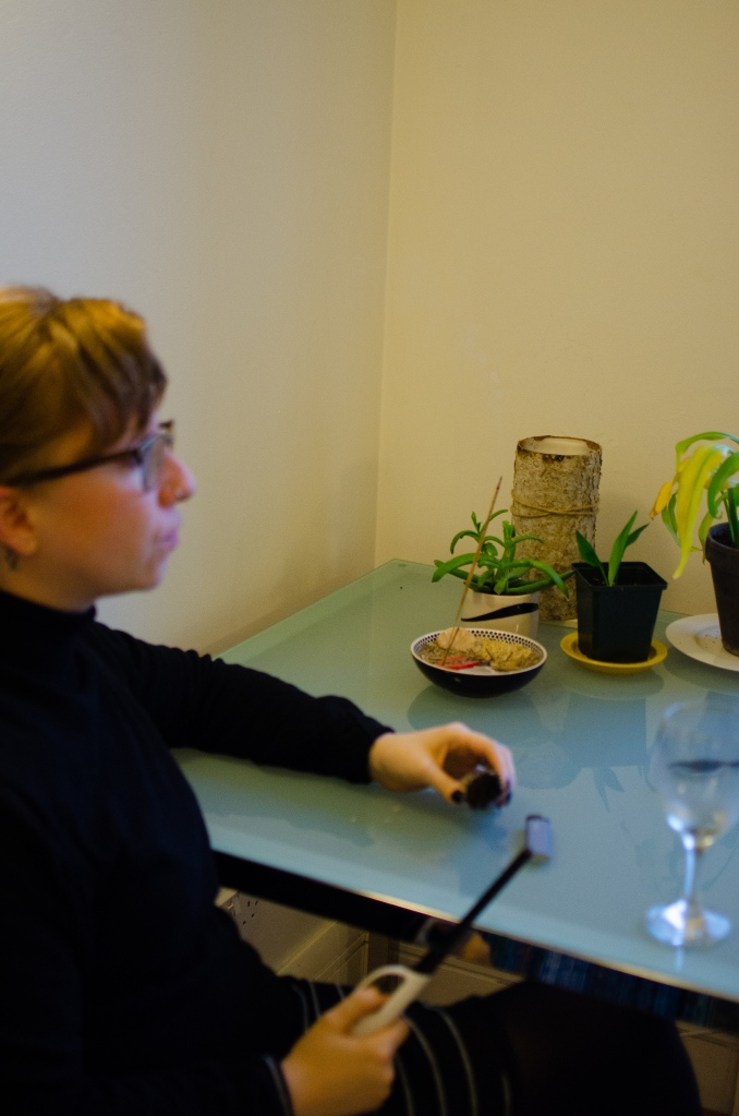 Nadia in the foreground, blurry, with incense in the background.