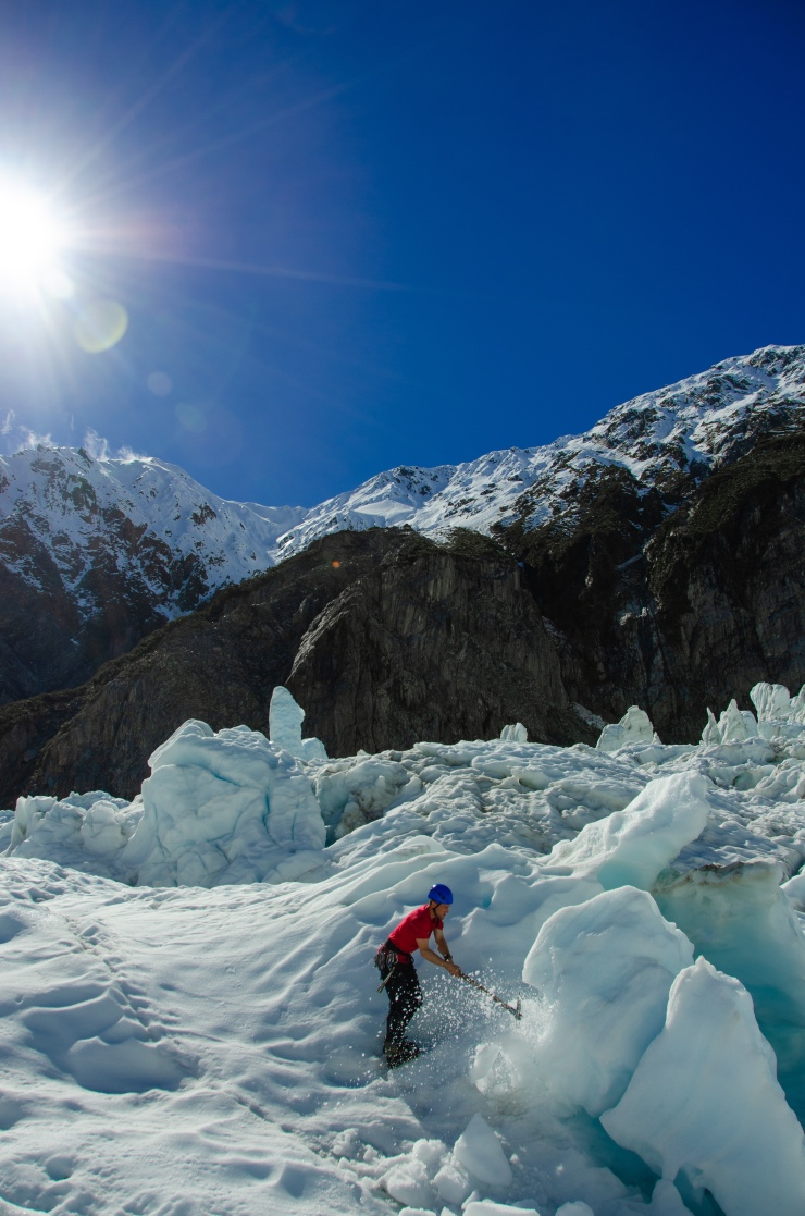 Hiker in red t-shirt hammering the ice in Franz Josef