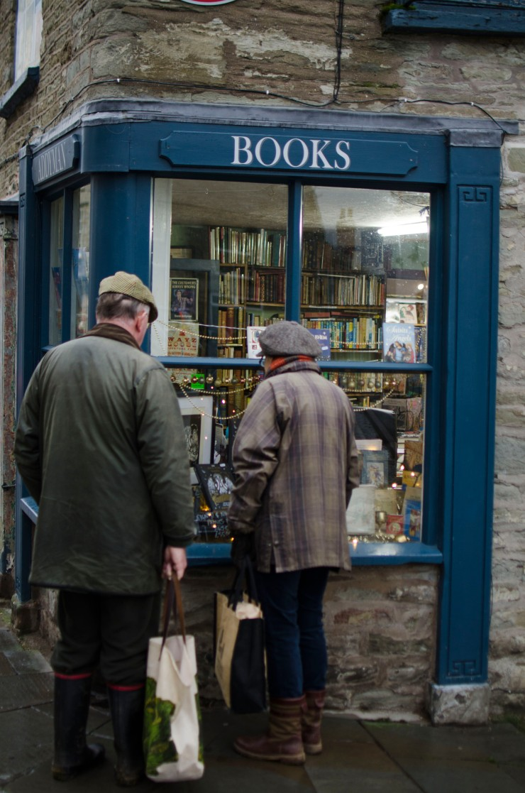 Onlookers enjoying a book window display in Hay-on-Wye
