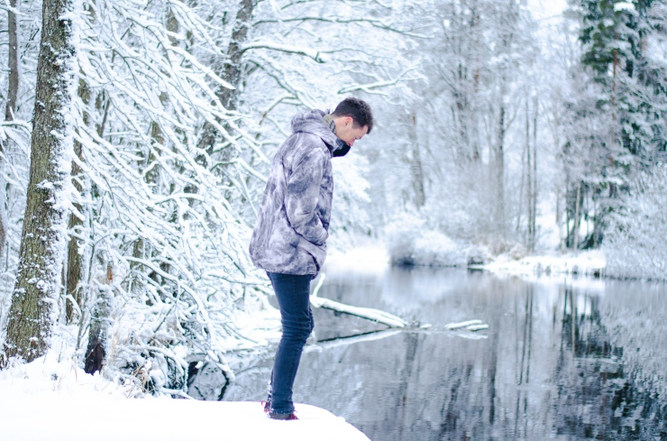 Man standing by the river in snowy Sweden