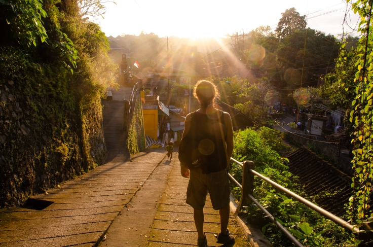 A man walking down a hill, facing the sunset in Ubud, Bali