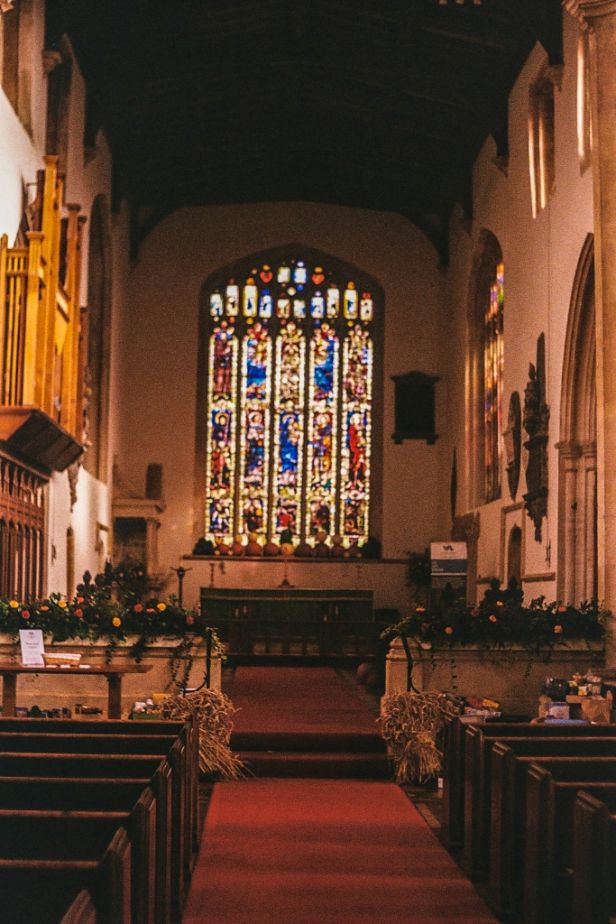 Interior of a church, featuring a glass window and autumnal plant decorations, all bathed in a red light