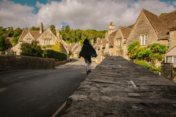 A woman wearing a blue cape walks away from the camera and into the village. The houses are lit by the sun while the bridge she's walking on is in the shade. Two onlookers look at ther in the background.