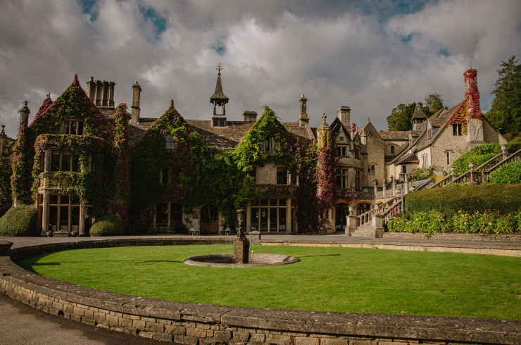 The Manor House, covered with green and purple ivy, against a background of moody grey clouds in the golden hour sunset