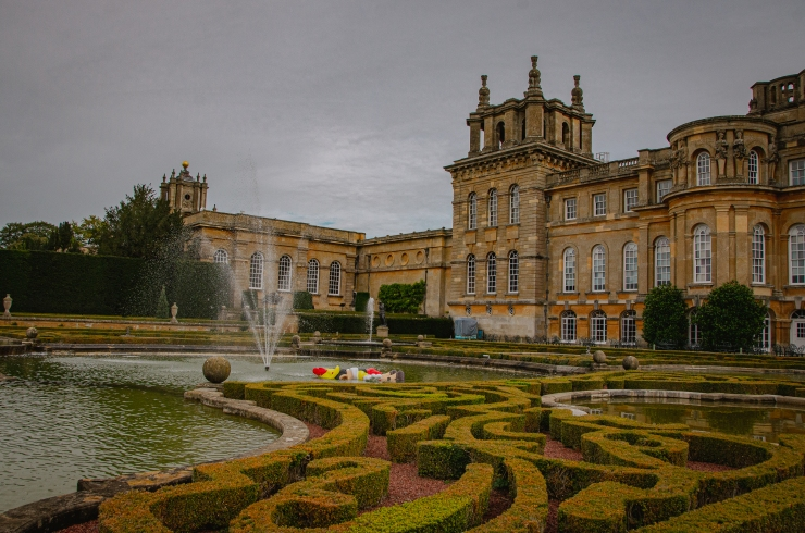 Blenheim Palace overlooking the French Garden, with a short bush mase and a fountain with a drowning Pinocchio, a Maurizio Mattalan installation