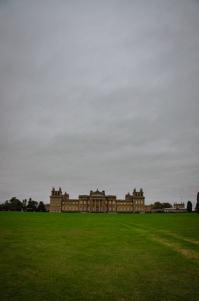 Blenheim Palace in the center of the frame, atop the main meadow, with a thick grey cloud mantel behind.