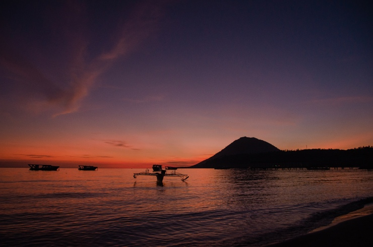 A traditional fishing boat, moored for the evening, at sunset in Pulau Bunaken, Indonesia