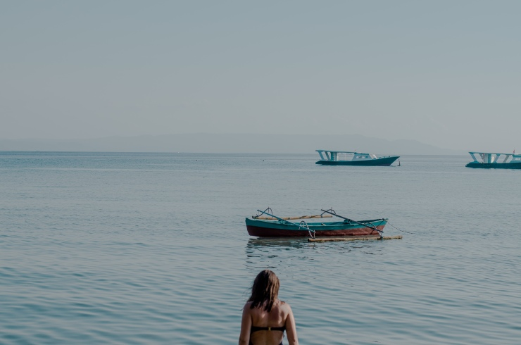 A woman walks into the sea in Pulau Bunaken, with traditional fishing boats in the background