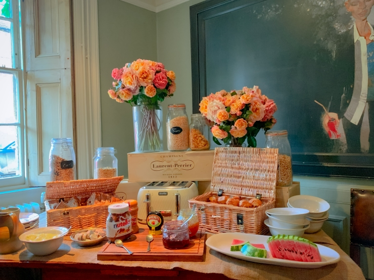 A colourful breakfast spread with fresh flowers, cereals, spreads, watermelon, yoghurt and pastries.