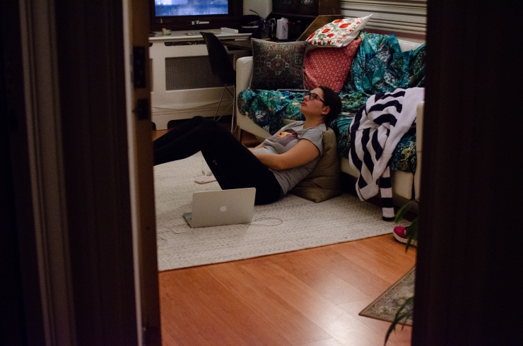 Woman laying on the floor and against a sofa, with her laptop near.