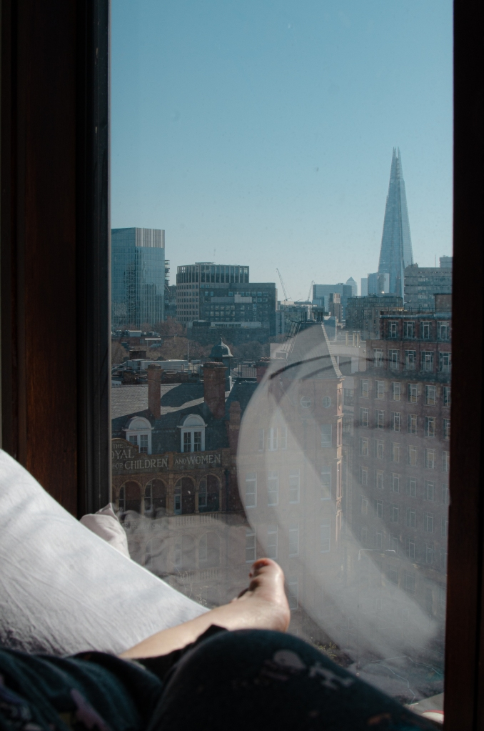 The Shard seen in the background behind a window, with a woman's foot in the center of the frame that indicates she's watching the city from the confines of her apartment.