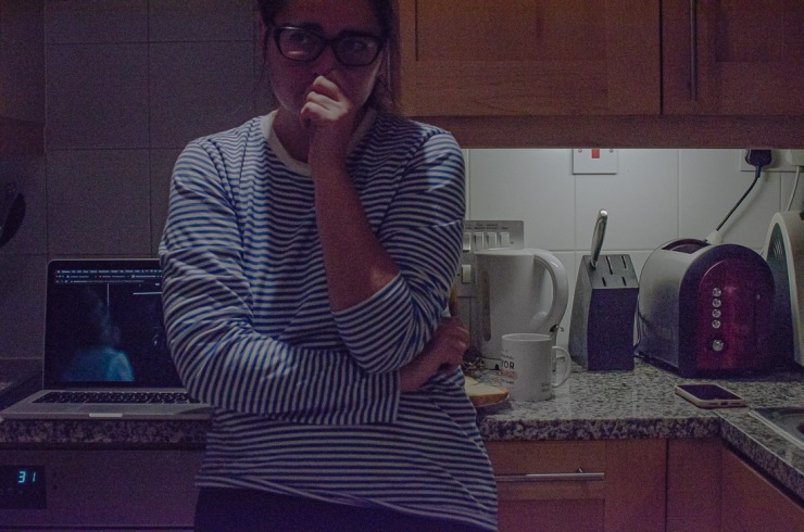 Self portrait of a femme woman staring into space off camera, having an anxiety attack in the kitchen