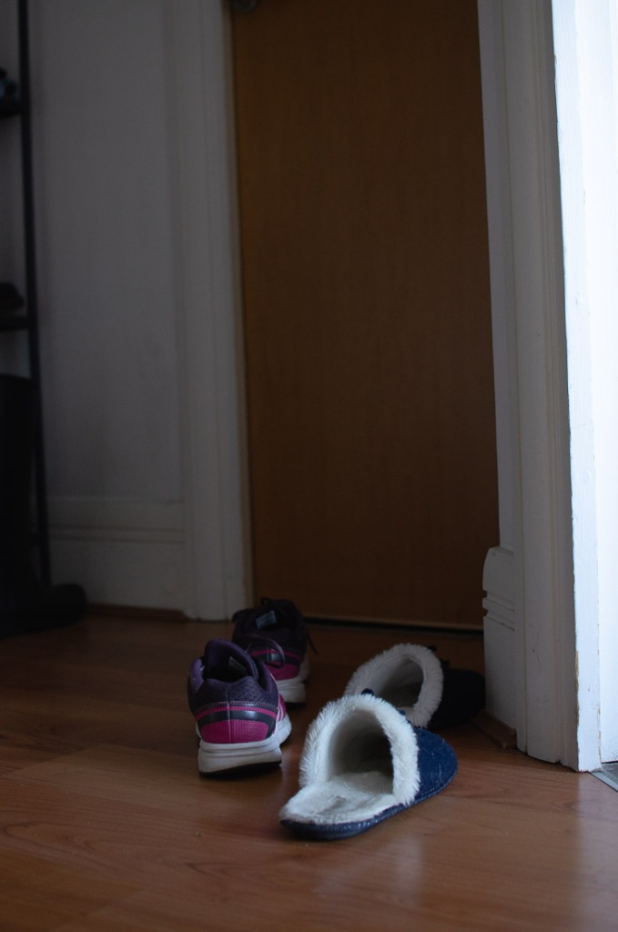 A pair of slippers and a pair of sports shoes left by a door frame, as if they had just been discarded
