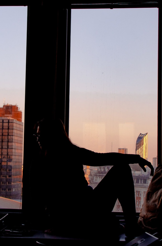 Self portrait of a femme woman posing on her window, only her silhouette
