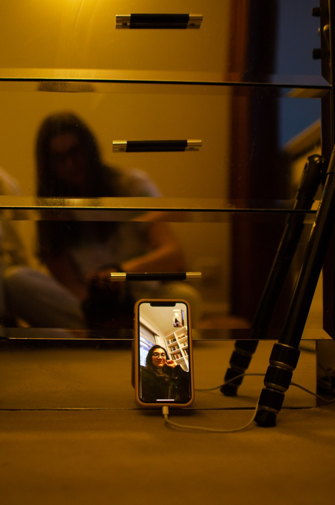 Self portrait of a femme women on a mirror shelf video calling a friend