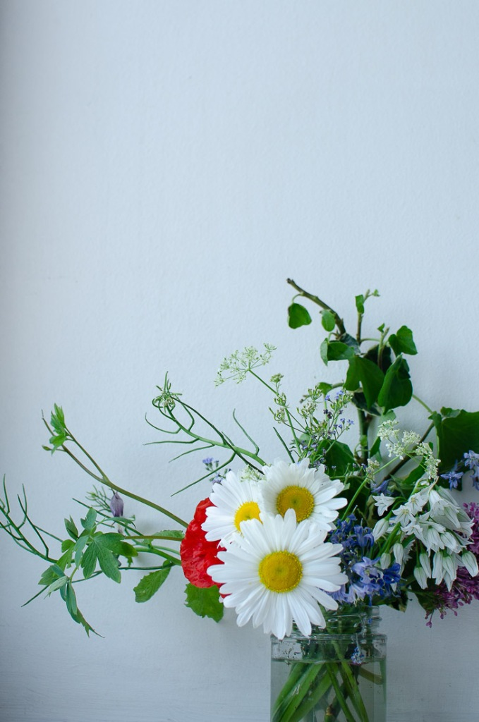 Still life of wild flowers against a white wall