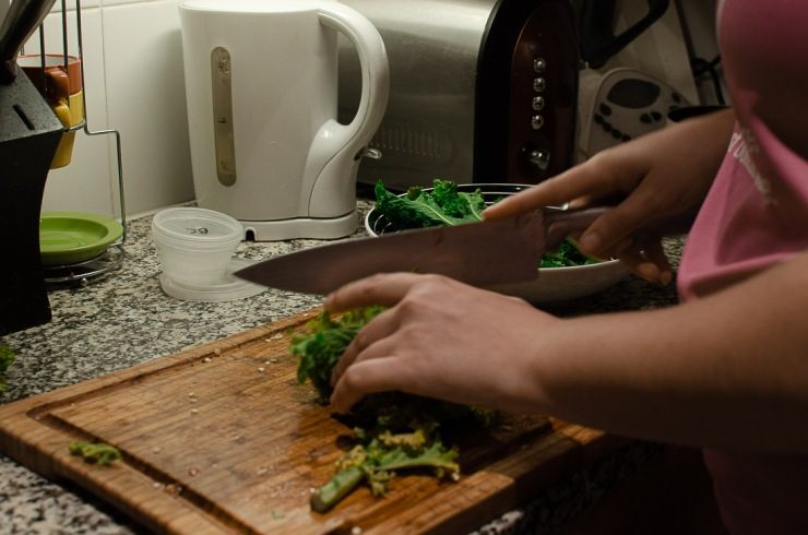 Close up of a woman's hands chopping kale on a wooden board on marble countertops