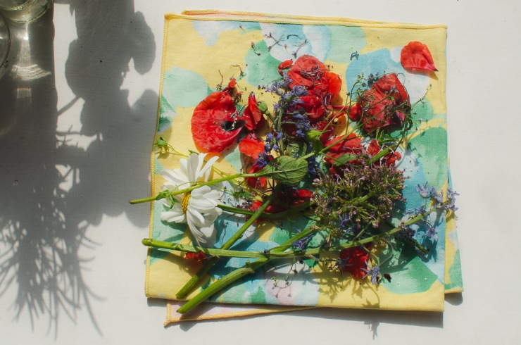 Flat lay of dead flowers on top of a colourful napkin