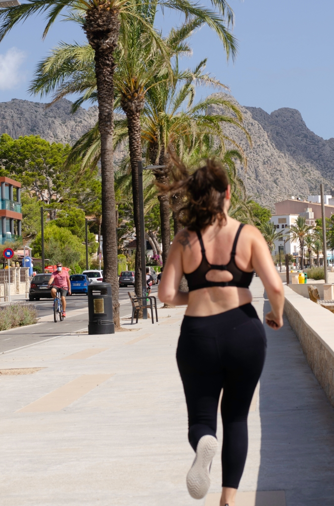 A white woman, with a dove tattoo on her left shoulder, runs away from the camera, wearing long black leggings and black sports top, beside a line of palm trees with mountains and short buildings in the distance.