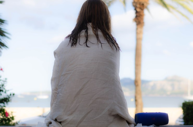 Woman staring into distance, wrapped with a thin blanket and with a blue speaker next to her